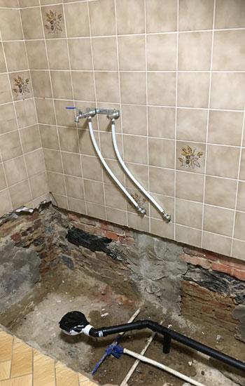Watertoevoer- en afvoer worden voorbereid voor de nieuwe douche wordt geplaatst